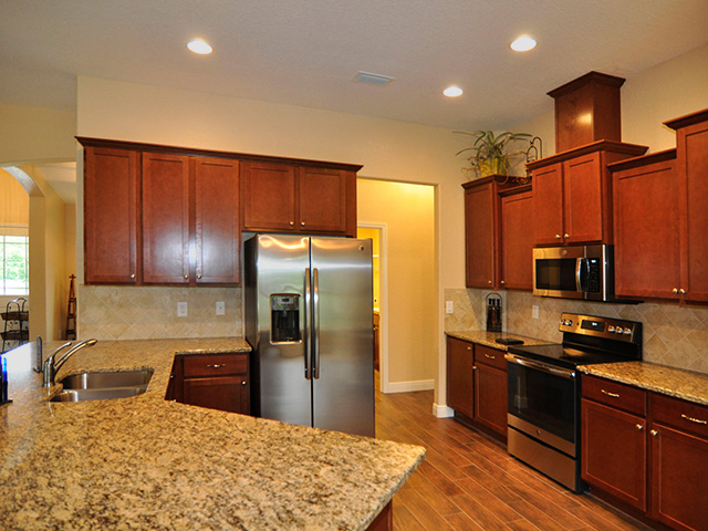 kitchen with wood panel cabinetry and granite countertop